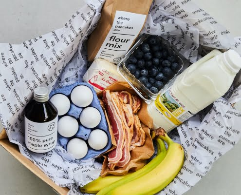 box containing pancake flour mix, maple syrup, buttermilk, eggs, butter, bacon, blueberries, bananas, recipe and tips