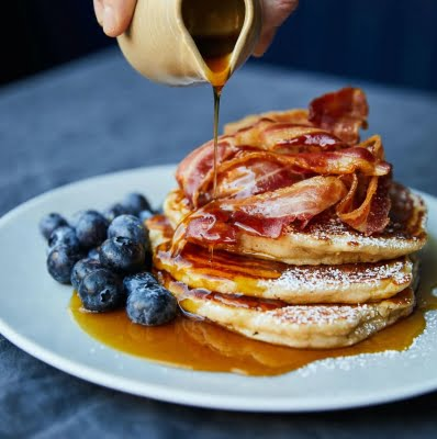 Pancakes on plate, blue berries, bacon, maple syrup pour
