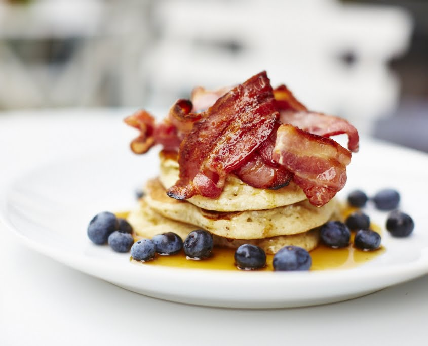 American pancakes, stacked, bacon, blueberries on white plate, maple syrup