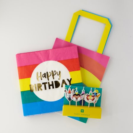 brightly coloured birthday gift package; includes colourful candles, birthday napkins, party poppers and celebration balloons
